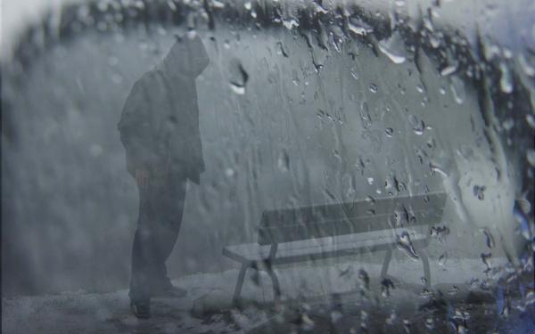 sad-boy-wearing-hood-standing-in-rain-with-bench-wide
